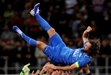 Former Italian soccer player Andrea Pirlo is lifted up at the end of his farewell soccer match at the San Siro stadium in Milan