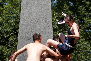 First year cadets at the U.S. Naval Academy climb the grease covered 21-foot Herndon Monument to end their freshman year in Annapolis, Maryland