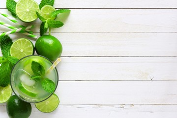 Sweet summer limeade. Top view side border with copy space on a rustic white wood background.