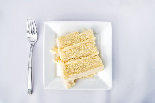 Flat top table setting lay view down closeup of restaurant or wedding reception white table tablecloth one plate with vanilla cream cake slice, fork