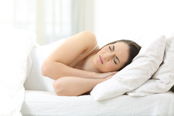 Unhappy woman sleeping on an uncomfortable mattress