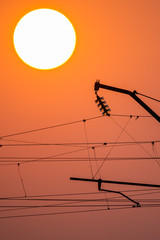 City electricity post pole during sunset with grey sky and sun in the background, silhouette