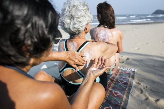 Senior women applying sunscreen