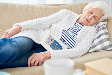 Portrait of white-haired senior woman falling asleep on couch lovingly hugging framed photograph of her husband at home alone photo in frame by me