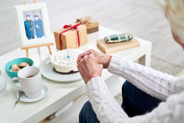 High angle portrait of unrecognizable senior woman nervously clasping her hands while celebrating birthday alone with photograph of her husband on table by birthday cake photo in frame by me .