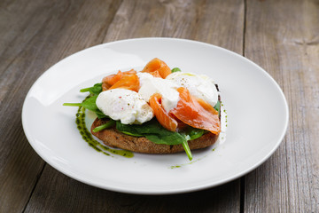 Wholemeal bread toast and poached egg with smoked salmon and spinach, healthy breakfast, restaurant menu photo, diet food