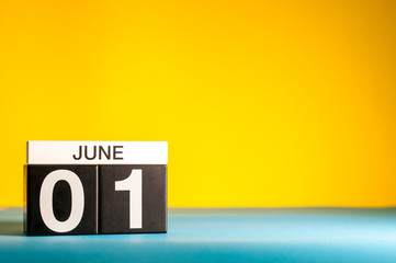 June 1st. Day 1 of june month, calendar on table with yellow background. Summer time, empty space for text