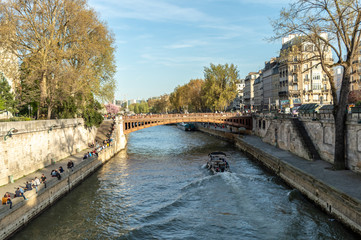The river Seine with a boat sailing and many people relaxing on the reiverside on a sunny day