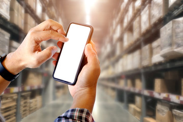 Cropped shot of man using smartphone in distribution warehouse.