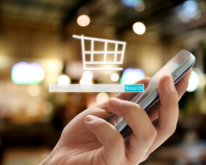 Hand of businessman holding a smartphone and have Shopping cart symbol to Search.