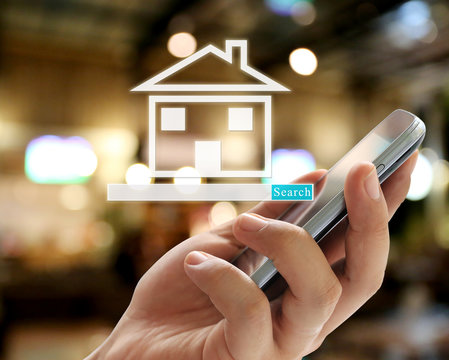 Hand of businessman holding a smartphone and have home symbol to search.