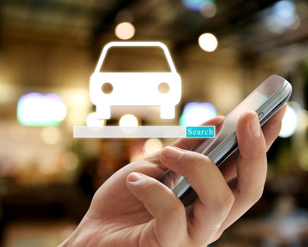 Hand of businessman holding a smartphone and have car symbol to search.