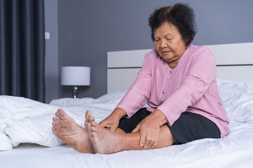 senior woman with leg pain in bed