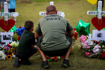 Mourners gather at a makeshift memorial left in memory of the victims killed in a shooting at Santa Fe High School in Santa Fe