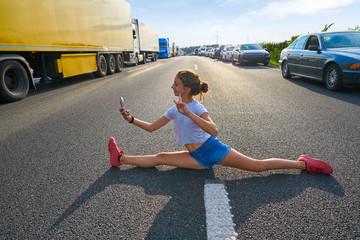 Split legs girl selfie photo in a traffic jam road