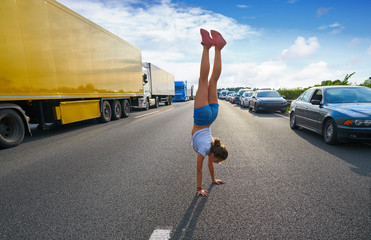 Hand stand girl in a traffic jam road