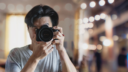 a man taking photography by digital mirrorless camera, with Bokeh light background