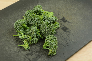 Chopped freshly rinsed raw broccoli florets on black weathered cutting board