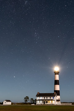 NAGS HEAD, NC - OCTOBER 27, 2017:  The Bodie Island Lighthouse shines beneath a canopy of stars near Nags Head, NC on October 27, 2017.