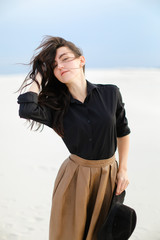 Young pretty woman wearing black blouse and brown skirt standing in white background and keeping hat. Concept of clothes collection and vogue.