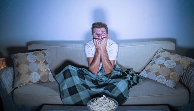 lifestyle portrait of attractive scared and nervous man watching suspense horror movie on television feeling stressed covering with blanket in panic