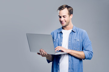 Smiling young man working with laptop