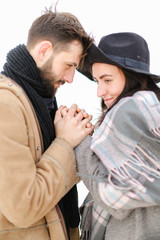 Portrait of young happy man holding woman hand in white background, wearing coat with scarf. Concept of couple seasonal winter photo session and romantic feelings.