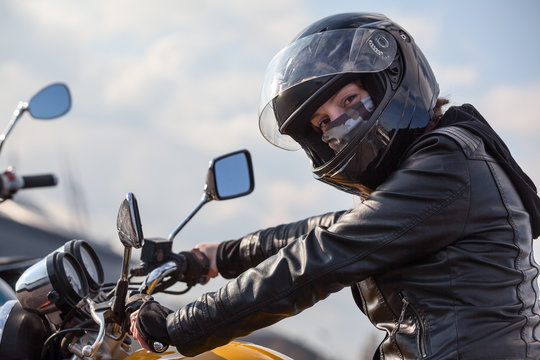 Motorcycle driver in black outfit holding steering wheel and looking at camera, Caucasian woman