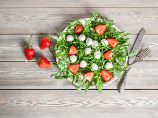 Delicious rucola salad with mozzarella and strawberries on a wooden background. Healthy foods. Top view