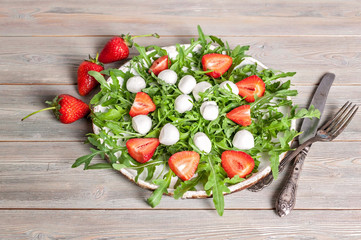 Delicious rucola salad with mozzarella and strawberries on a wooden background. Healthy foods