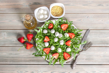 Delicious rucola salad with mozzarella, strawberries, olive oil and spices on a wooden background. Healthy foods