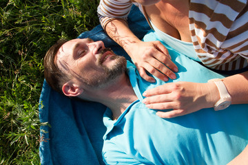 Portrait of man with woman hands on his chest. Smiling man laying on blue blanket and green grass with hands of girlfriend