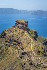 Volcanic rock formation with hiking trail on the island of Santorini, Greece