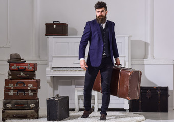 Macho stylish on strict face stands and carries big vintage suitcase. Man, traveller with beard and mustache with baggage, luxury white interior background. Baggage and travelling concept.