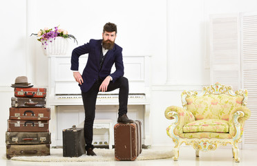 Macho elegant on thoughtful face standing near pile of vintage suitcase. Man, traveller with beard and mustache with luggage, luxury white interior background. Luggage and travelling concept.
