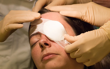 Doctor covering eye of patient by medical plaster