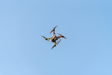 Drone with camera on blue sky. New technology for bird eye view photography.