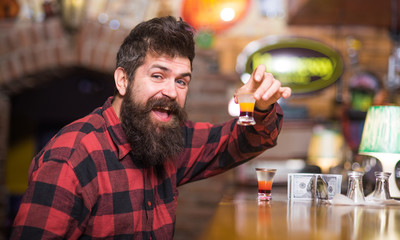 Hipster holds glass with alcoholic drink, short cocktail.