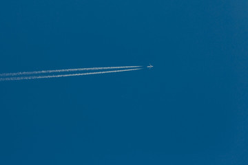World Travel Vacation Tourism Concept. Jet plane draws an inversion trail in the blue sky