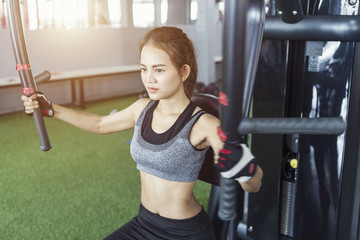 Sport young woman working out on a fitness exercise with equipment at the gym.