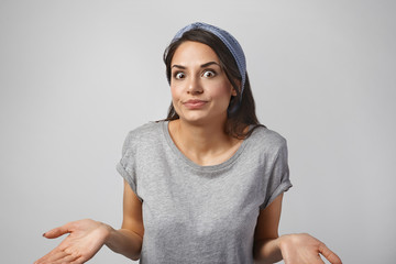 Picture of startled bug eyed clueless young brunette woman wearing headband and gray t-shirt expressing doubt and confusion, being at loss, doesn't know how to react, feeling completely puzzled