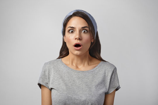 Beautiful shocked girl being at panic because she forgot to switch off iron before leaving home. Picture of astonished amazed young female opening mouth widely, staring at camera in amazement