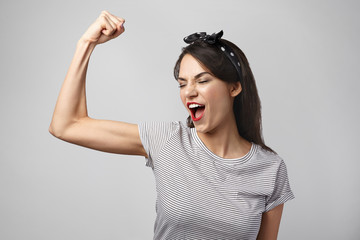 Picture of excited young brunette woman in casual clothes opning mouth widely while screaming, showing off muscles, tensing bicep, demonstrating power and energy. Sports, fitness and strength concept