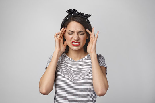 Portrait of beautiful stressed young woman grimacing, clenching teeth and massaging temples, having headache or migraine because of terrible sound or noise. People, health, pain and sickness