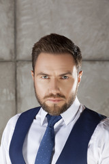 Portrait of fashionable handsome man with beard and hair style wearing tie, white shirt and blue vest suit
