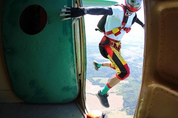 Skydiver is jumping out of a plane.
