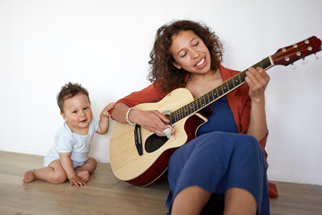 Horizontal shot of beautiful young female singer sitting on floor at home, holding acoustic guitar, performing songs to cute baby son. Hispanic mother entertaining little child with musical instrument