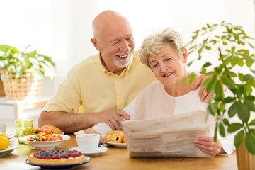 Happy senior woman reading newspaper during breakfast with smiling husband