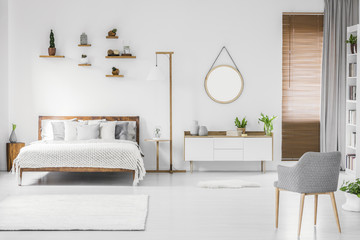 Spacious designer white bedroom interior with wooden bed with bedding and pillows, night-table,...