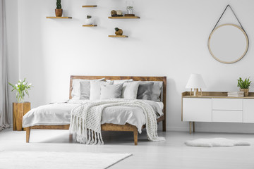Comfortable big wooden framed bed with linen, pillows and blanket, nightstand beside and round mirror hanging on a white wall in a bright bedroom interior. Real photo.